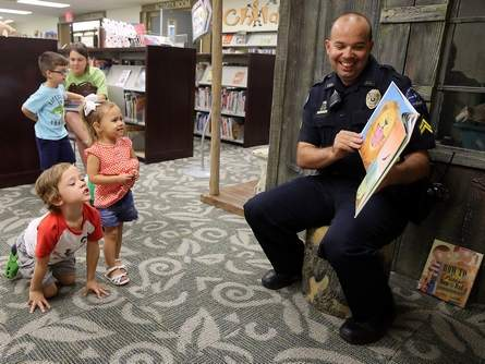 Detective Douglas Fontana reads to kids at the library