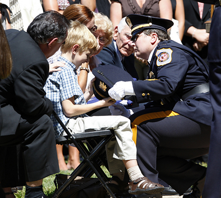 20080816FC  15/x   Tyler Zerby, 6, is given his father's hat by North Brunswick police Lt. Lisa Racz, at the funeral for North Brunswick Poice Lt. Christopher Zerby, at Franklin Memorial Park in North Brunswick on Saturday August 16, 2008.   Zerby was killed earlier in the week in an automobile accident with another officer.  NORTH BRUNSWICK, NJ  8/16/08  2:15:48 PM  FRANK H. CONLON/THE STAR-LEDGER