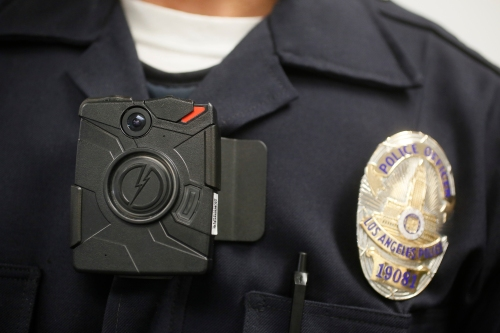 "FILE - In this Jan. 15, 2014 file photo, a Los Angeles Police officer wears an on-body camera during a demonstration for media in Los Angeles. The fatal police shooting of the unarmed black teenager in Ferguson, Mo. has prompted calls for more officers to wear so-called ""body cameras,"" simple, lapel-mounted gadgets that record the interactions between the public and law enforcement. (AP Photo/Damian Dovarganes, File)"